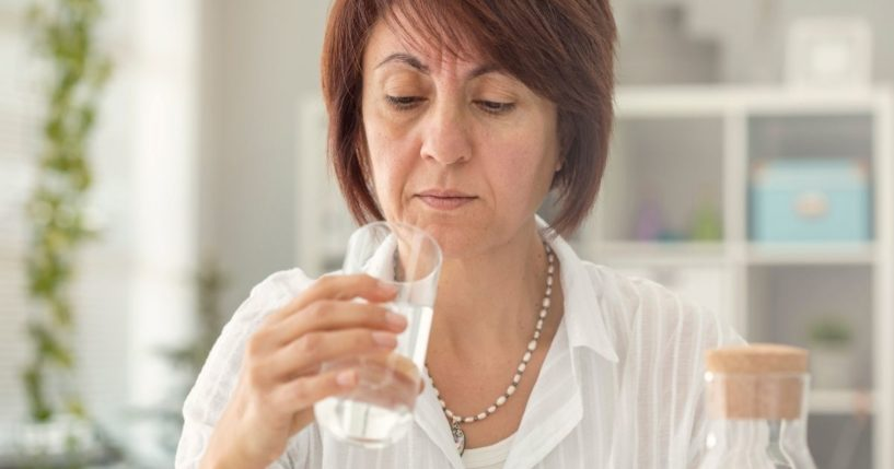 The above stock photo shows a woman looking at her water glass.