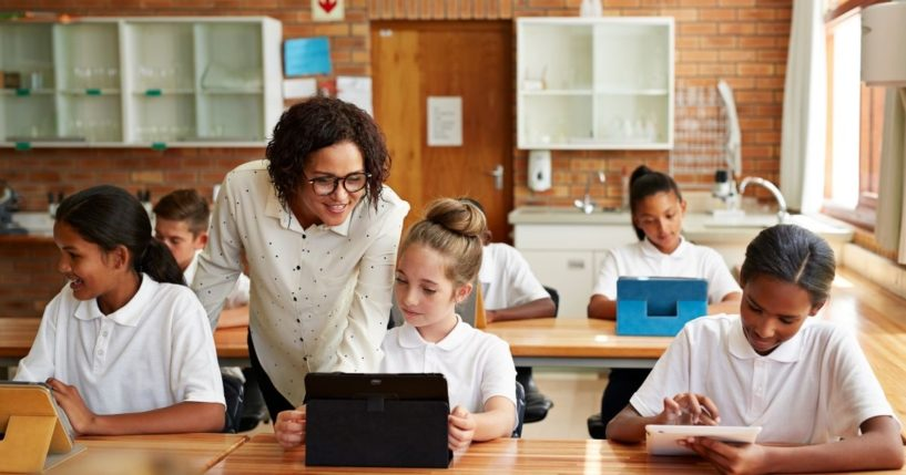 The above stock photo shows a teacher helping a student with a tablet in the classroom.