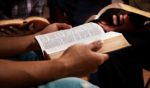 This stock photo portrays a group of young adults reading their Bibles together. Black theologian Voddie T. Baucham, an American-born pastor who now lives in Zambia, discusses what the Bible has to say about racism.