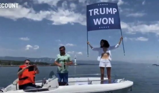 """Noor bin Ladin, Osama bin Laden's niece, protests in Geneva by holding up a flag which says """"Trump Won."""""""