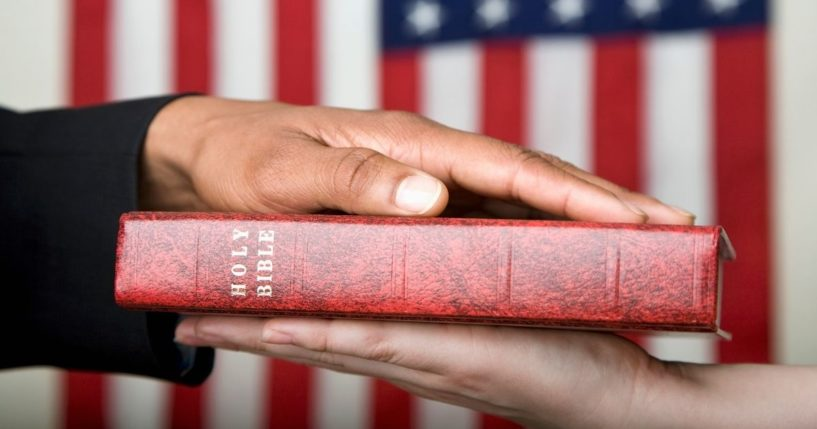 """This stock image portrays a person swearing on the Bible in front of an American flag. HarperCollins Christian Publishing, Zondervan's parent company, retracted an agreement to print a """"God Bless the USA"""" Bible edition."""