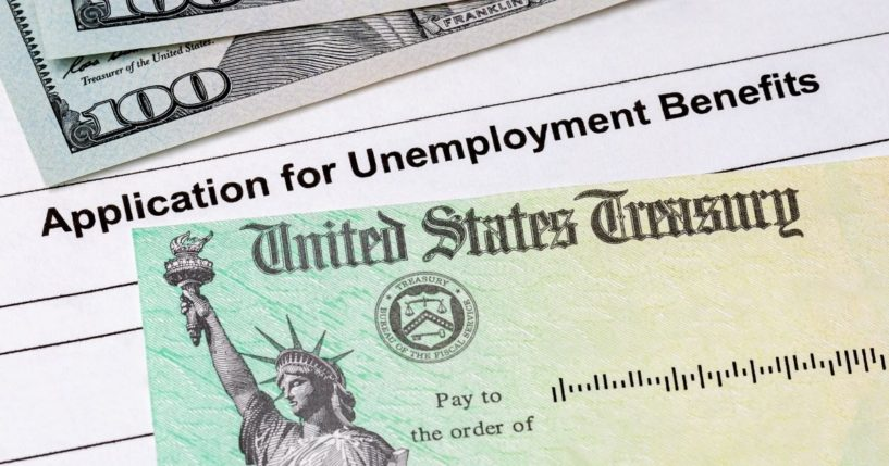 An application for unemployment benefits is pictured alongside bills and a check.