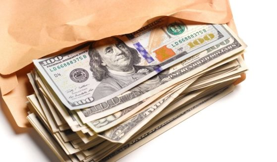 This stock image portrays an envelope full of cash. One study is now suggesting that families can receive up to six figures from the federal government while on unemployment.