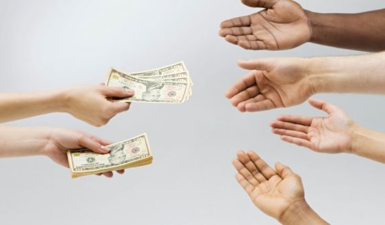 This stock photo portrays a person holding out money to outstretched hands. On Saturday, nine states will join Iowa, Mississippi and Missouri in ending their pandemic-related unemployment benefits early.