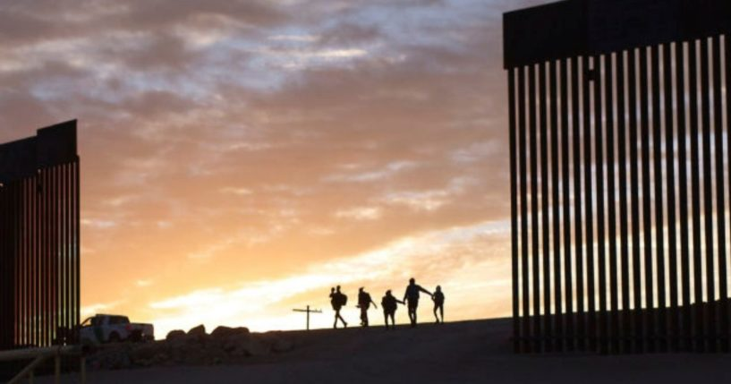 A pair of migrant families from Brazil passes through a gap in the border wall to reach the United States after crossing from Mexico in Yuma, Arizona, on Thursday.