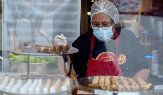 A worker wears a mask while preparing desserts at the Universal City Walk, in Universal City, California, on May 14, 2021.