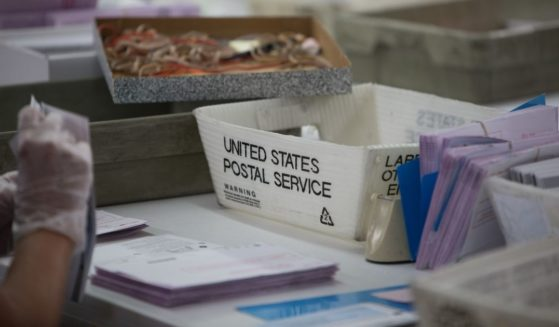 Election poll workers count vote-by-mail ballots from United States Postal Service boxes during Nevada's June 2020 primary election.