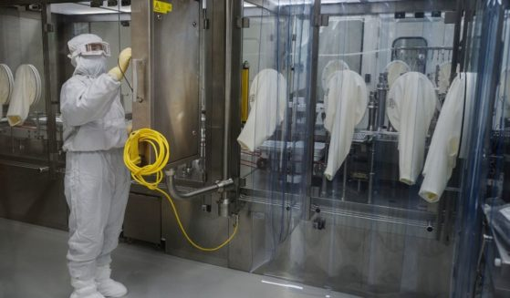 A worker in protective gear is pictured in a Beijing plant where the Sinovac Biotech firm is producing a vaccine against COVID-19 made from an inactivated form of the coronavirus.