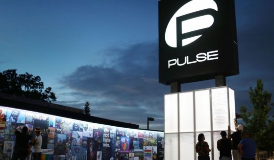 People on June 11, 2018, visit the memorial set up for the 49 patrons who were killed at the Pulse Nightclub in Orlando, Florida, two years earlier.