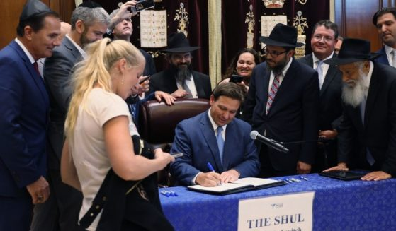 Florida Gov. Ron DeSantis signs a bill at The Shul of Bal Harbour on June 14, 2021, in Surfside, Florida. The bills, HB 529, requires Florida schools to hold a daily moment of silence.