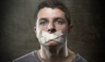 """A man with tape in an """"X"""" shape over his mouth."""