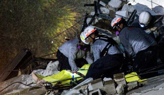 Emergency crews remove a covered stretcher bearing the body of a victim of Thursday morning's condominium collapse in Surfside, Florida.