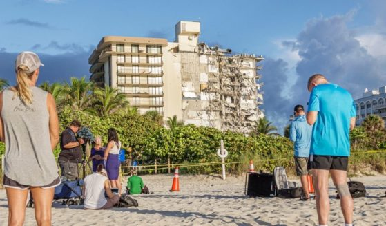Reporters and bystanders view the wreckage of the collapsed Champlain Towers South in Surfside, Florida.