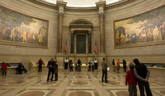 Visitors in the National Archives Rotunda take in murals celebrating the nation's founding.