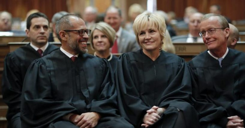 In this Jan. 14, 2020 file photo, Iowa Supreme Court Justices Christopher McDonald, left, Susan Christensen, center, and Edward Mansfield, right, attend Iowa Gov. Kim Reynolds' Condition of the State address at the Statehouse in Des Moines, Iowa.