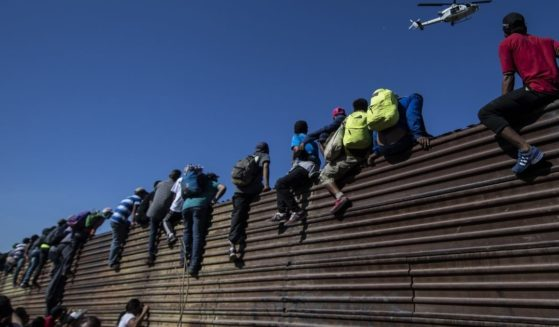 A group of Central American migrants -- mostly Hondurans -- climb a metal barrier on the Mexico-U.S. border near El Chaparral border crossing, in Tijuana, Baja California State, Mexico, on Nov. 25, 2018.