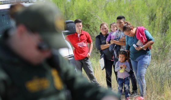 Central American asylum seekers wait as U.S. Border Patrol agents take groups of them into custody on June 12, 2018, near McAllen, Texas.