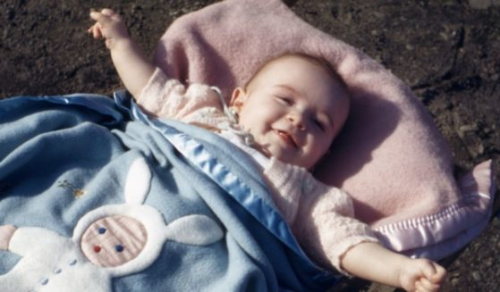 A 1994 film photo shows a baby girl of approximately one year wrapped in a blue bunny-themed blanket as she smiles.