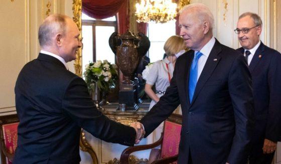 US President Joe Biden, right, shakes hands with Russian President Vladimir Putin prior to a meeting in Geneva on Wednesday.