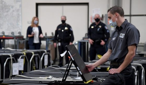 A Clark County election worker checks a voting machine among others that are boxed up at the Clark County Election Department on Nov. 6, 2020, in North Las Vegas.
