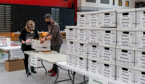 Poll workers check a box of absentee ballots at Sun Prairie High School on Nov. 3, 2020, in Sun Prairie, Wisconsin.
