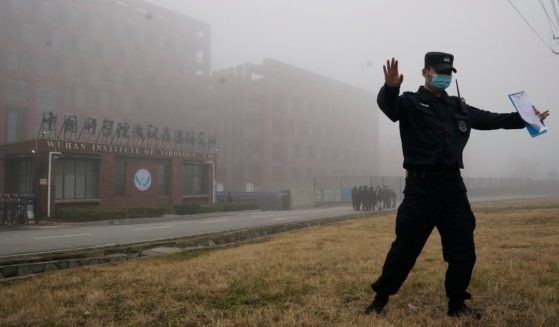 A security official moves reporters away from the Wuhan Institute of Virology in China's Hubei province after a World Health Organization team arrived for a field visit on Feb. 3, 2021.