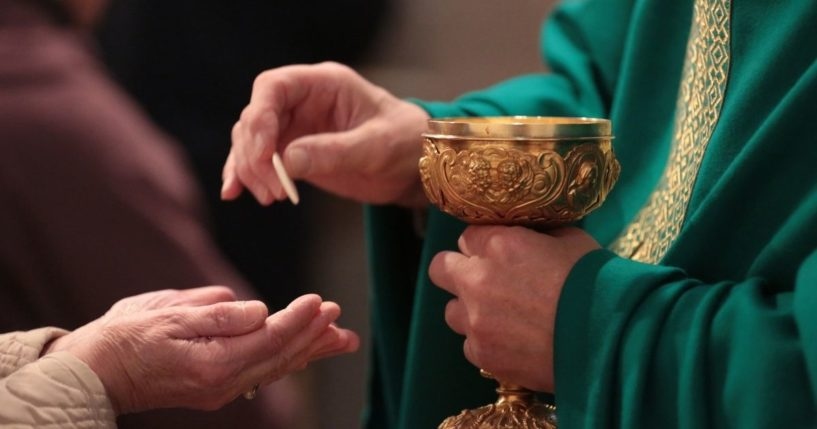 A priest administers communion in the above stock image.