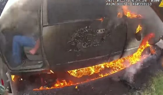 Officer Eddie Pineda opening the door to rescue the man trapped inside a burning truck on May 24 in Austin, Texas.