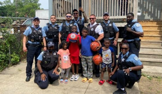 A group of Chicago police officers pose with the kids they bought a basketball hoop for.