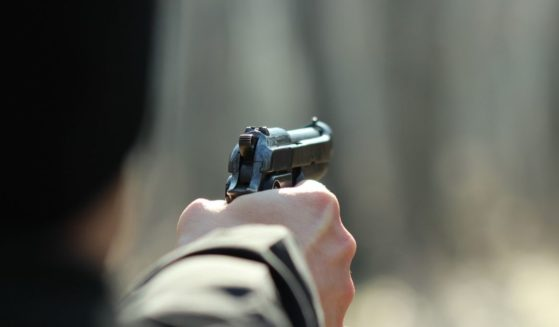 A man uses a gun in the above stock image.