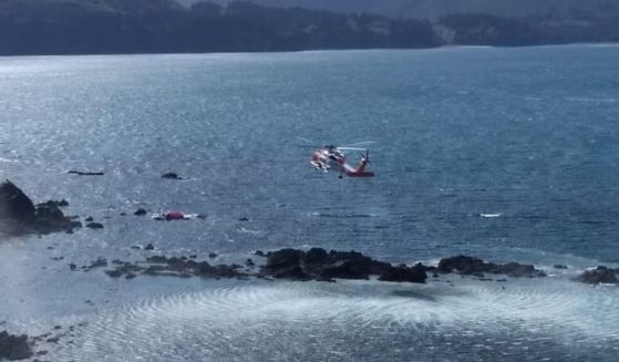 The U.S. Coast Guard rescuing three people and two dogs whose raft got blown against a rocky outcropping in Kodiak, Alaska, on June 5.