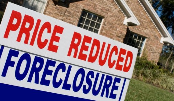 A foreclosure sign appears in front of a house in the above stock image.