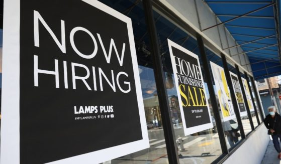 """A pedestrian walks by a """"Now Hiring"""" sign outside of a Lamps Plus store on June 3, 2021, in San Francisco."""