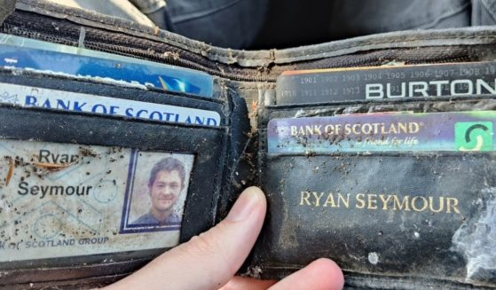 Ryan Seymour holding his old wallet, which had been stolen and thrown into a bush where it stayed for nearly 20 years before finding its way back to him.