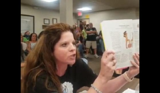 Becky Swan, a parent in Bloomington, Illinois, holds a sex education book during a school board meeting last week.
