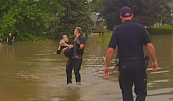 A police officer carries an 82-year-old woman who nearly died in her car after it was swept off the road by floodwaters.
