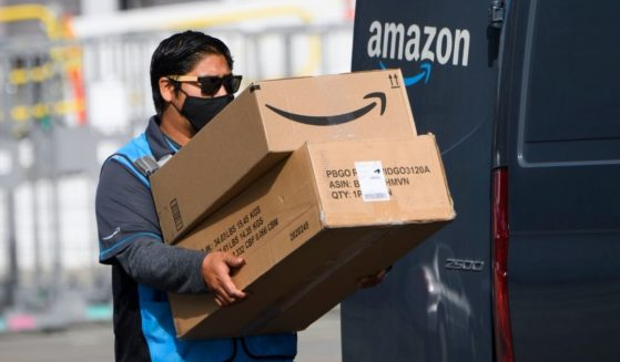 An Amazon.com Inc. delivery driver carries boxes into a van outside of a distribution facility on Feb. 2, 2021, in Hawthorne, California.