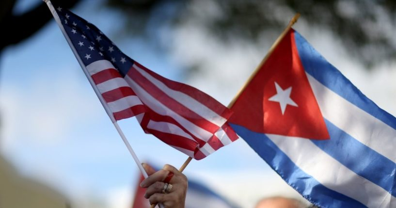 A woman holds an American flag and a Cuban one at a protest on Dec. 20, 2014, in Miami.