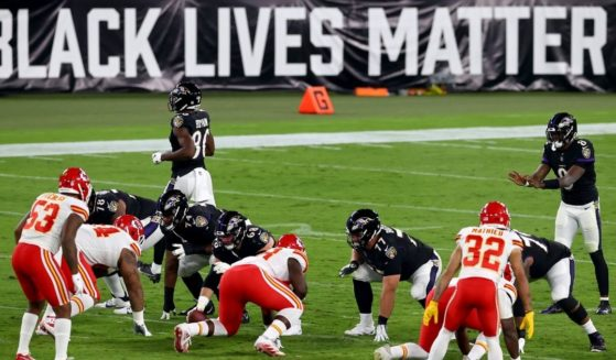 """Baltimore Ravens quarterback Lamar Jackson waits for the snap in front a large """"Black Lives Matter"""" banner during a game against the Kansas City Chiefs at M&T Bank Stadium in Baltimore on Sept. 28, 2020."""