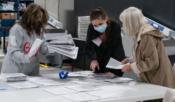 Election personnel sort absentee ballot applications for storage at the Gwinnett County Board of Voter Registrations and Elections offices on Nov. 7, 2020, in Lawrenceville, Georgia.