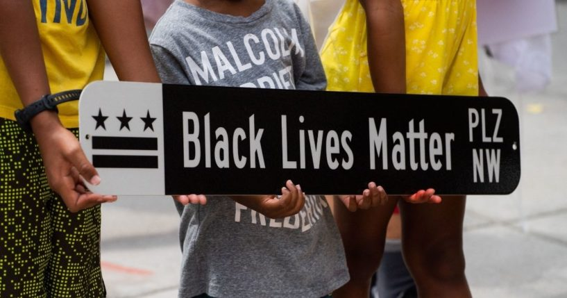 Children pose for a photograph with a Black Lives Matter Plaza street sign at Black Lives Matter Plaza in Washington, D.C., on June 19, 2021, during a Juneteenth celebration.