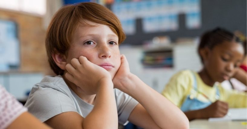 A boy looks tired and bored as he sits at his desk in a classroom.