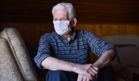 This stock image portrays a man wearing a mask, looking out the window. The Centers for Disease Control and Prevention is expected to update its guidance on mask-wearing again.