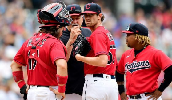 Shane Bieber (No. 57) of the Cleveland Indians gets a visit at the mound during a game against the Seattle Mariners at Progressive Field on June 13.