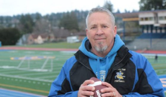 Former high school football coach Joe Kennedy, with a football in his hand a football field in the background.