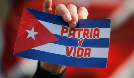 """A Cuban resident in Chile holds a sign reading """"homeland and life"""" during a protest against the Cuban government outside the Cuban Embassy in Santiago on Friday."""
