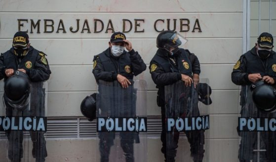 Police officers stand guard outside the Cuban Embassy during a demonstration of Cuban citizens residing in Peru against the Cuban government of President Miguel Díaz-Canel in Lima on Tuesday.