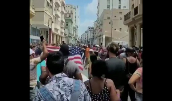 Cuban protesters wave an American Flag as they march against the communist regime in Havana.