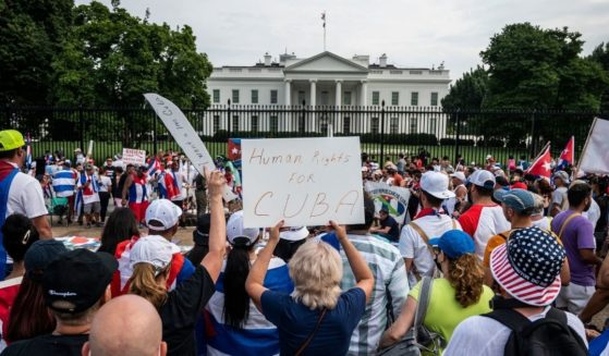 Protesters hold up signs during a demonstration in front of the White House on Sunday in Washington D.C.