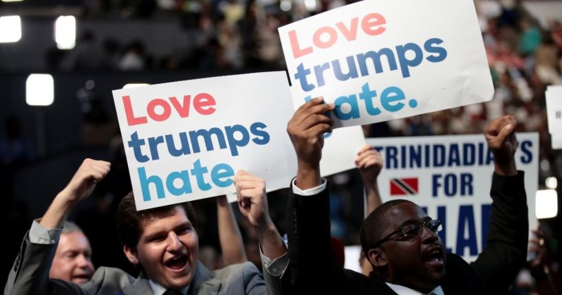 """Delegates hold up signs that read """"love trumps hate"""" during the opening of the first day of the Democratic National Convention at the Wells Fargo Center on July 25, 2016, in Philadelphia."""